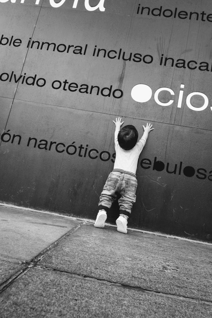 """Un niño (mi hijo) intenta alcanzar la palabra """"Ocio"""" grabada en una pared de hierro pero no llega bien. La foto está retocada en blanco y negro para darle yo qué sé qué le añade a la foto pero está muy bien."""